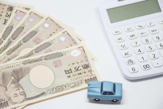 現金と電卓と車のおもちゃ