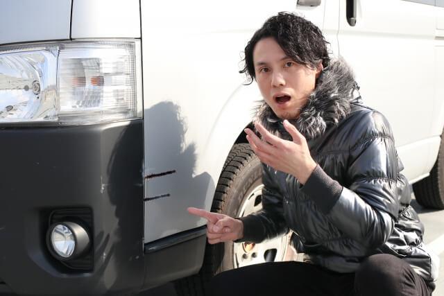 車にキズがついて驚く男性
